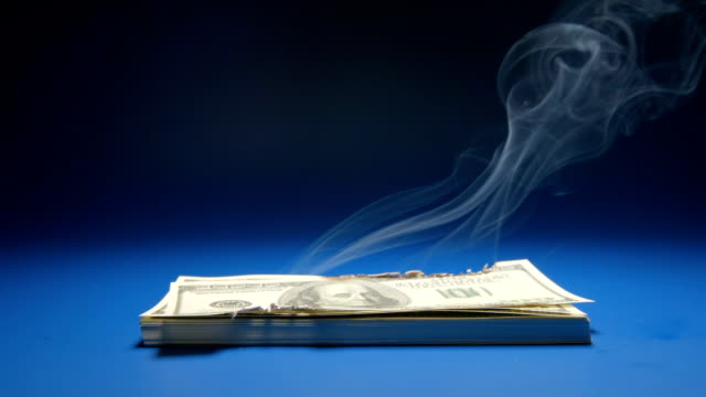 SLOW MOTION: Heap of paper money (US dollar) smoking video
