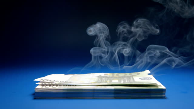 SLOW MOTION: Heap of paper money (Euro) smoking video