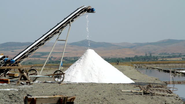 Heap of sea salt crystals under conveyor belt video