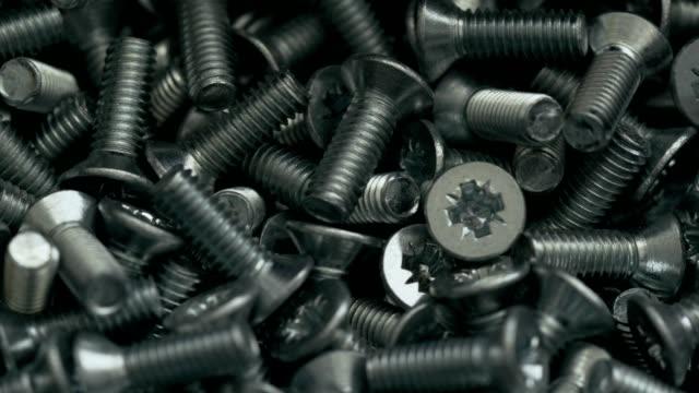 Heap of short metal countersunk bolts video