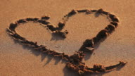 Heart drawn in sand video