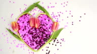 Heart made of pink confetti framed by tulips video
