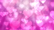 Heart particles on pink background video