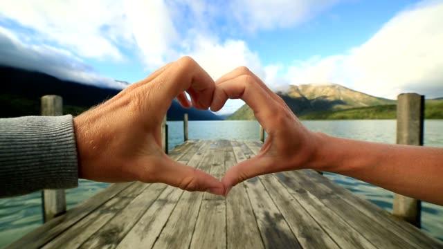 Heart shape finger frame on natural landscape video