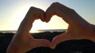 Heart shape finger frame on seascape at sunset video
