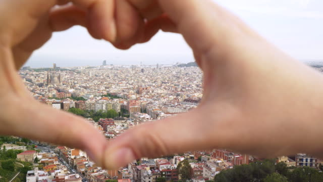 Hearth symbol made with hands above Barcelona city. video