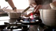 Heating ginger root on stove fire. Person heating vegetable ginger on fire stove video