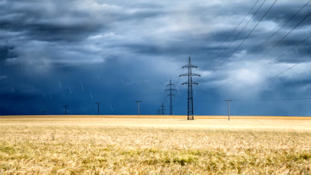 Heavy clouds bringing thunder, lightnings, storm and rain over a wheat field and electric pylons video