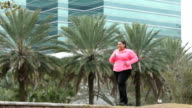 Heavy Hispanic woman power walking with hand weights video