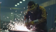 Heavy industry worker at a factory is working with metal on a angle grinder while hot sparks are produced in a result. video