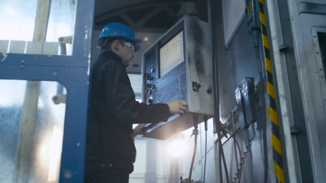 Heavy industry worker is using a control panel computer in a factory. video