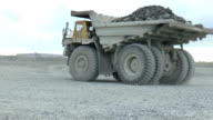 Heavy mining dump trucks moving along the opencast video