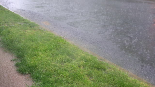 Heavy rain storm on a road drops on water surface. video