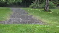 Heavy rain water drops falling on garden stone pavement and splashing in rainy day. FullHD video
