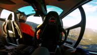 POV helicopter passenger looking at pilot flying over a forest area video