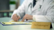 Hematologist prescribing treatment for hemophilia, filling out medical forms video