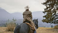 SLO MO Herdsman riding his horse on mountain video