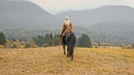 SLO MO Herdswoman riding her horse across mountain meadow video