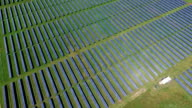 High Aerial Fly Looking Down at the Sun Reflecting off Solar Panel Arrays in a Huge Solar Power Plant video