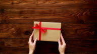 High angle of hands putting a nice present box on a wooden background video