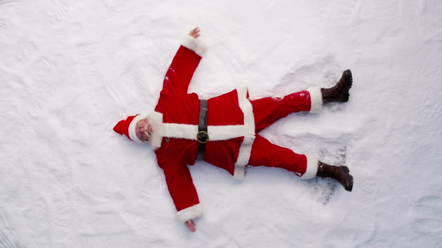 High angle shot of Santa Claus making a snow angel video