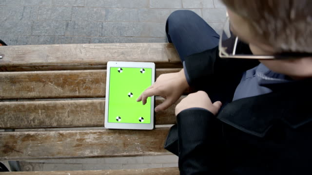 High Angle View Of A Man Working With Tablet On A Bench, Vertical Shot, Green Screen video