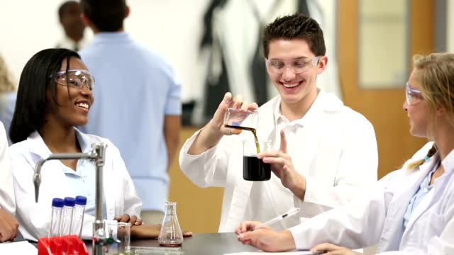 High school chemistry student leading science group experiment video