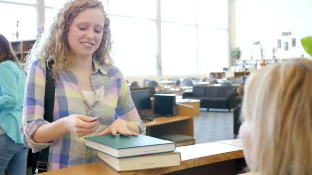 High school girl checking out books at library checkout counter with library ID card video
