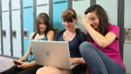High school girls look at laptop computer video