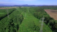 AERIAL: High voltage electricity towers and power lines in nature video