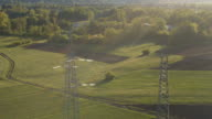 AERIAL: High voltage power lines and electricity steel pylons on meadow field video