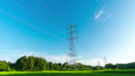High voltage towers over paddy field with sky background time lapse video