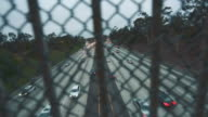 Highway traffic shot from behind fence on bridge during afternoon hours video