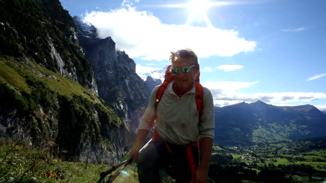 Hiker ascends path through mountain meadow video