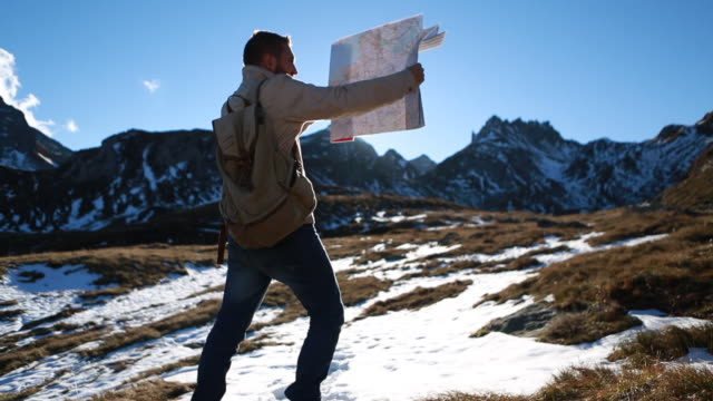 Hiker checks map at sunrise by mountain range video
