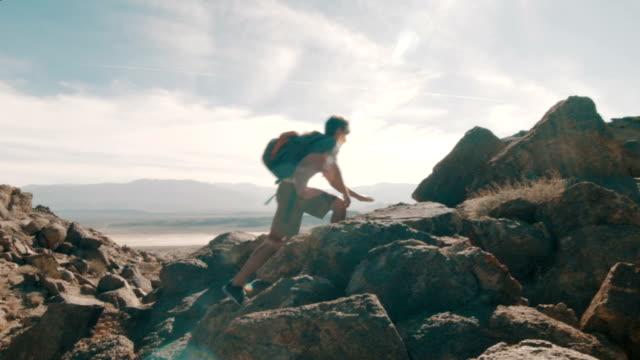 Hiker Climbing Atop Rocks video