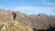 Hiker climbs mountain ridge crest, looks at map for directions video