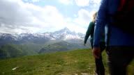 Hiker couple walk across mountain meadow video