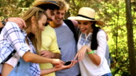 Hiker couples watching smartphone video