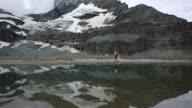 Hiker follows shoreline of lake below Matterhorn video