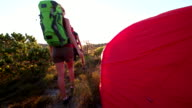Hiker leaving their tent as they go hiking at sunrise video