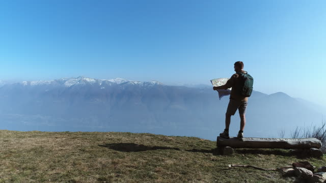 Hiker looking at map from mountain top video