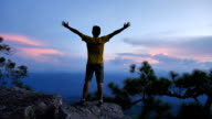 Hiker man stretching arms on the top of a mountain video