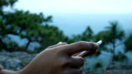 Hiker man using by phone in the mountains video