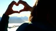 Hiker on mountain top above clouds make heart shape finger frame video