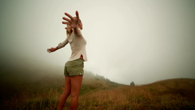 Hiker reaches foggy top, arms outstretched video