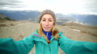 Hiker reaches mountain top and takes selfie video