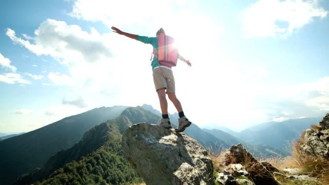 Hiker reaches mountain top, arms outstretched video
