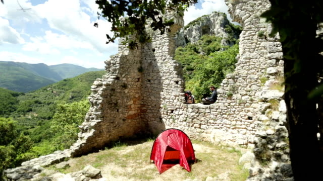 Hiker relaxes on stone wall while writing journal, beside tent video