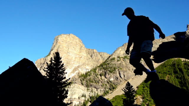Hiker silhouetted again mountians video